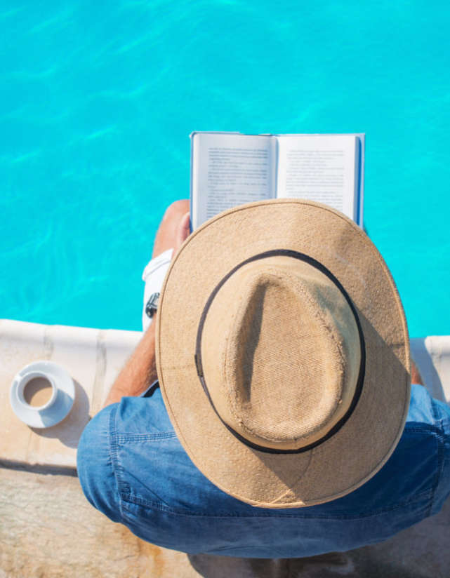 guy reading a book by the pool