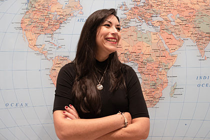 Carmen Muñoz-Fernández in front. of a world map