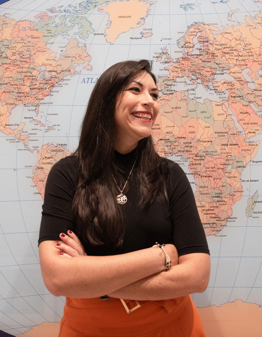 Carmen Muñoz-Fernández in front. of a world map